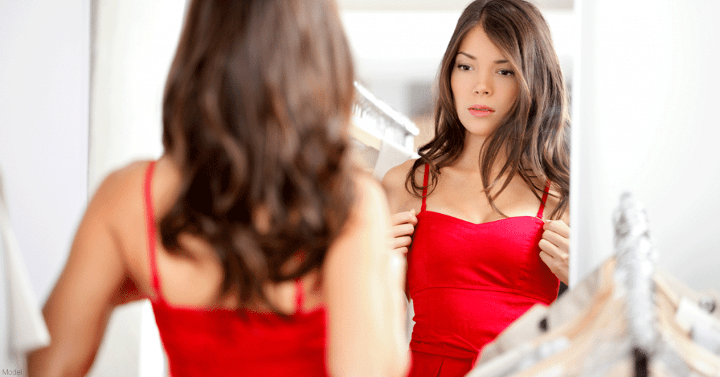 Woman in red dress contemplating breast augmentation surgery